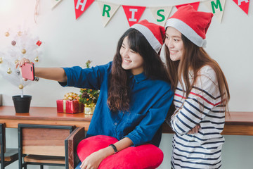 Young beautiful Asian Woman friends using smartphone to selfie together.Smiling face in room with Christmas tree decoration for holiday background.Party and celebration concept.