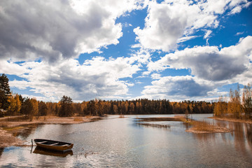 Autumn colored landscape of the finnish lake blue bright vibrant sky with clouds Finland