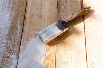 brush with white paint on a wooden background. painting the wood with white paint.