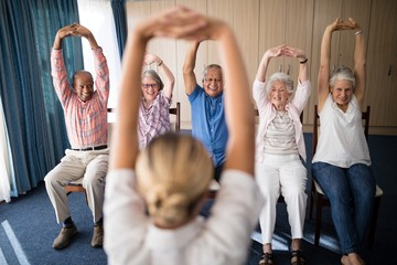 Cheerful senior men and women exercising with female doctor