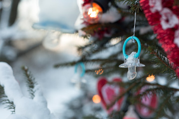 Christmas background of a baby's dummy / pacifier / comforter or soother on a Xmas tree. Baby's first Christmas concept.