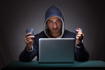 Young man wearing a hoodie sitting in front of a laptop computer
