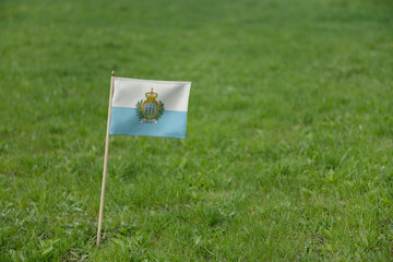 San Marino flag on a green grass lawn field background. National flag of San Marino waving outdoor
