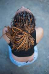 Beautiful young woman with hairdread hair dreadlocks, sunny open, no face