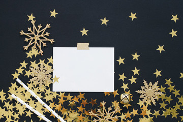 Christmas planning concept mock up. Note on black background with washi tape, gold stars confetti, serpentine and glitter snowflakes. Place for text flat lay