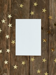 Mock up greeting card on wood rustic background with Christmas gold stars confetti. Invitation, paper. Place for text flat lay