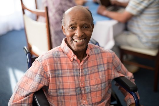 Portrait of smiling disabled senior man sitting on wheelchair
