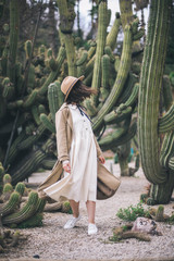 Brunette young lady walks in cacti park wearing old fashioned white dress and brown hat