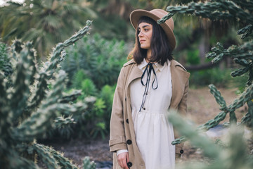 Happy brunette woman walks garden fool of wild desert cacti in old fashioned wedding white dress and brown hat