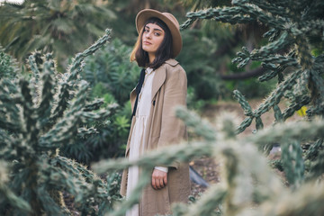Dreamy brunette girl walks in cacti park wearing old fashioned white dress and brown hat
