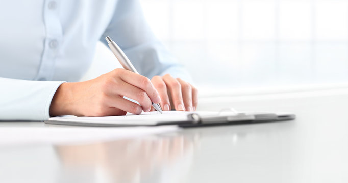 Woman's hands writing on sheet  in a clipboard with a pen, isolated on desk