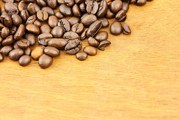 Coffee beans on brown wood background with copy space.
