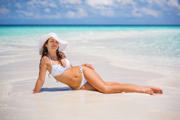 Young woman in bikini and hat relaxing on the beach
