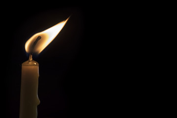 a burning candle on a dark background.