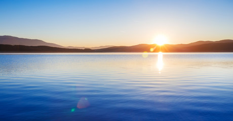 Wonderful Sunrise over lake scenery in blue and yellow colors. Panoramic side ratio photo.
