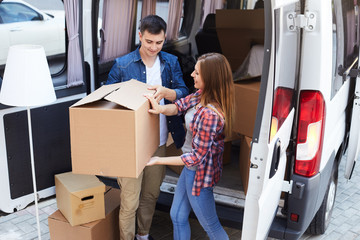 Portrait of smiling young man and woman unloading big cardboard boxes from moving van outdoors