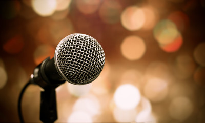Blurred of microphones in seminar room, talking speech in conference hall light with microphone and keynote. Speech is vocalized form of communication humans, vintage tone