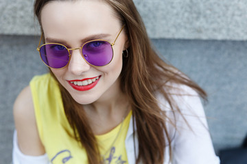 Close up portrait of stylish young woman in sunglasses smiling outdoors