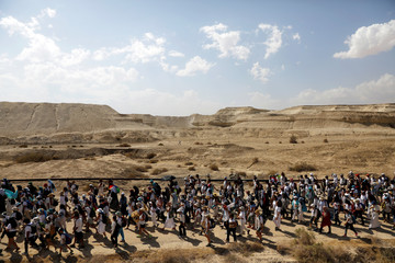 """Palestinian and Israeli women march, as part of an event organised by """"Women Wage Peace"""" group calling for an end to the Israeli-Palestinian conflict, near the Jordan River, in the occupied West Bank"""