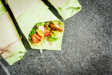 Mexican food. Healthy eating. Wrap sandwich: green lavash tortillas with spinach, fried chicken, fresh greens salad, tomatoes, yoghurt sauce. Black dark stone table. Copy space top view