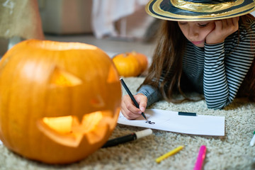 Portrait of pretty little girl wearing Halloween costume drawing laying on floor by carved pumpkin