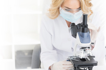 Female doctor looking through a microscope