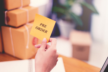 """""""Pre-Order"""" text on post it paper in woman hand at post office with many boxes, Online shopping and Marketing concept idea. Split and cross processing tone pinterest and instragram like process."""