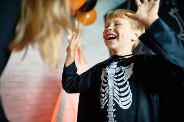 Waist-up portrait of laughing little boy wearing skeleton costume enjoying Halloween home party, blurred background