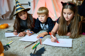 Cute little friends wearing fancy costumes lying on cozy carpet at living room decorated for celebrating Halloween and drawing with colorful felt-tip pens