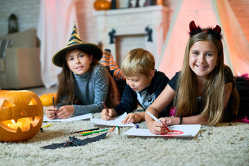 Group portrait of cheerful children wearing Halloween costumes gathered together at cozy living room decorated for Halloween and drawing colorful pictures, girls looking at camera with wide smiles