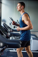 Profile view of young sporty man in headphones doing cardio exercise on treadmill, interior of modern gym on background