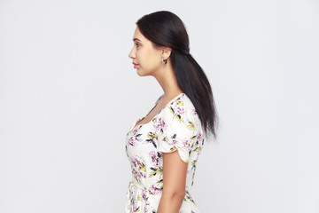 Side view of beautiful young adult woman, standing alone at gray background.