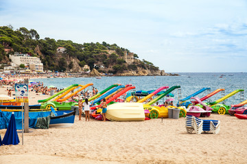 Beach off the coast of Lloret de Mar, Costa Brava. People on the beach in spain lie on sun loungers under umbrellas. Resting under a castle on the beach in Lloret de Mar.