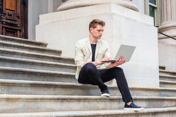 Young American Man with little beard studying, working in New York, wearing beige blazer, black pants, casual shoes, sitting on stairs in office building on campus, reading, working on laptop computer