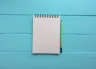 Notebook with a spring and a pencil. Bright blue, turquoise surface. Painted Board. Close-up with copy space. Top view
