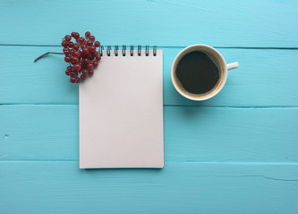 Notebook with a spring, branch with viburnum berries and a Cup of coffee. Bright blue, turquoise surface. Close-up copy space.