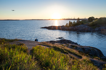 Tiny people couple is enjoying summer sunset by the sea in Helsinki Finland