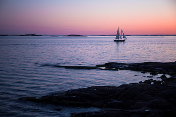 Lonely sailboat in the Baltic sea during colorful sunset time near Helsinki Finland