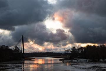Heavy sunset about the lake and suspension bridge in Vanhakaupunki Helsinki Finland