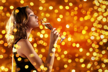 christmas theme, woman drinks a glass of sparkling wine on blurred lights