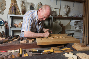 Maestro tallista trabajando la madera con martillo y gubia.
