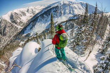 Man standing at top of ridge. Ski touring in mountains. Adventure winter freeride extreme sport