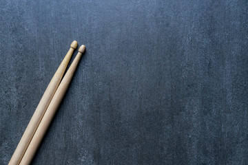 Drum stick on black table background, top view, music concept