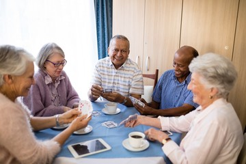 Multi-ethnic senior friends playing cards at table