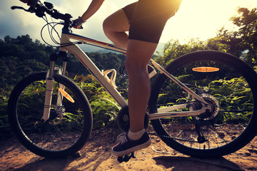 woman cyclist cycling on summer forest trail