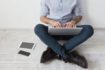 Cropped image of stylish tattooed hipster guy wears shirt, jeans and boots, sits crossed legs on floor, keyboards on laptop, surf socia networks, checkes newsfeed online. Man surrounded with gadgets