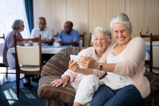 Portrait of smiling senior woman taking selfie with friend