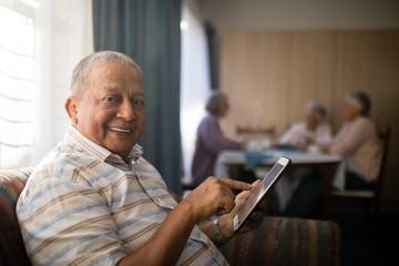 Portrait of smiling senior man using digital tablet