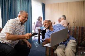 Happy senior man showing laptop to friend