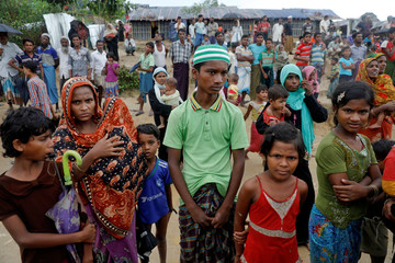 Rohingya refugees wait for some aid to be distributed at a camp for those who recently fled from Myanmar, near Cox's Bazar